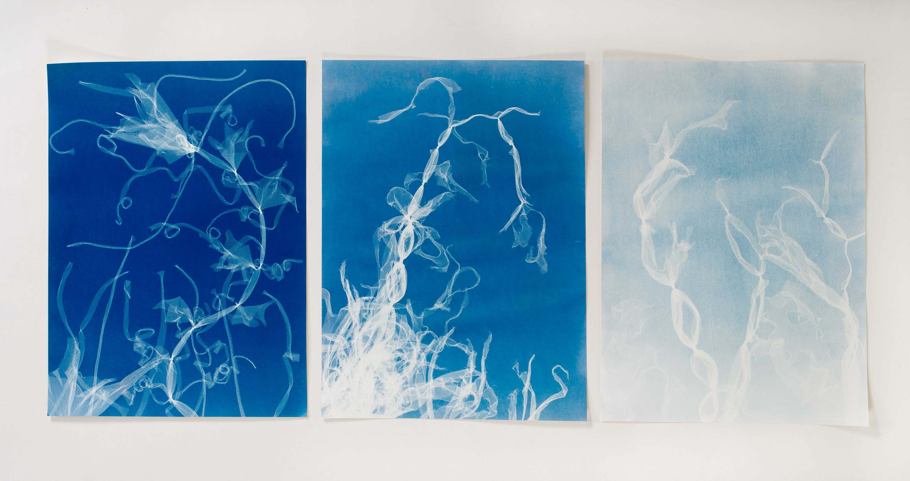 three panes of white wisps against blue backgrounds that get darker from left to right