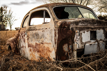 rusted car body in a field