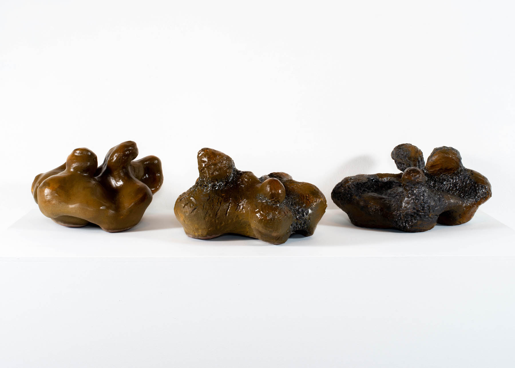 three brown ceramic pieces of varying shapes