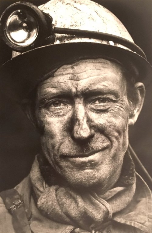 An image of a man's face smudged with coal wearing a miner's helmet