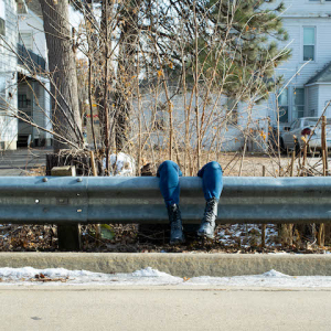 legs hanging over guardrail along a road with houses in the background