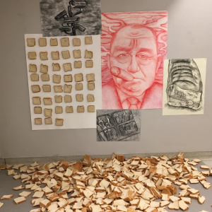various artwork on a wall with sliced bread in a pile on the ground in front