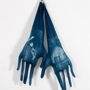 gloves tacked to a wall with images of home depicted on them